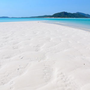 View along white sand on Whitehaven Beach to aqua water and nearby islands