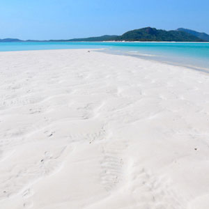 View along the white sand on Whitehaven Beach to aqua water and nearby islands