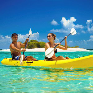 A man and woman paddling a kayak through aqua water by a sandy tropical island
