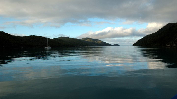 A cloudy sky reflected in the calm water of Nara inlet, surrounded by the hills of Hook Island