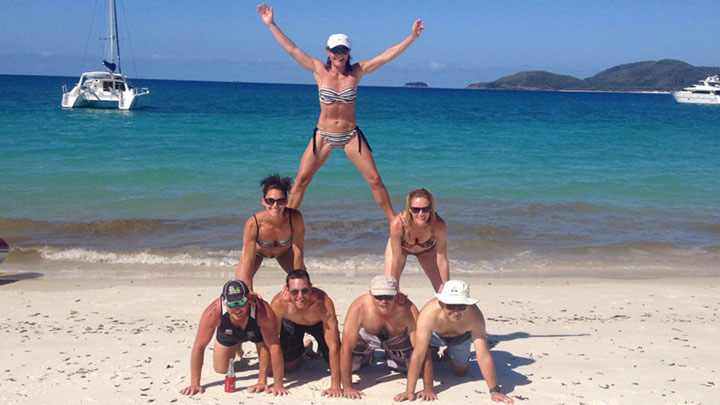 Men and women on a Whitsunday beach form a human pyramid on the sand
