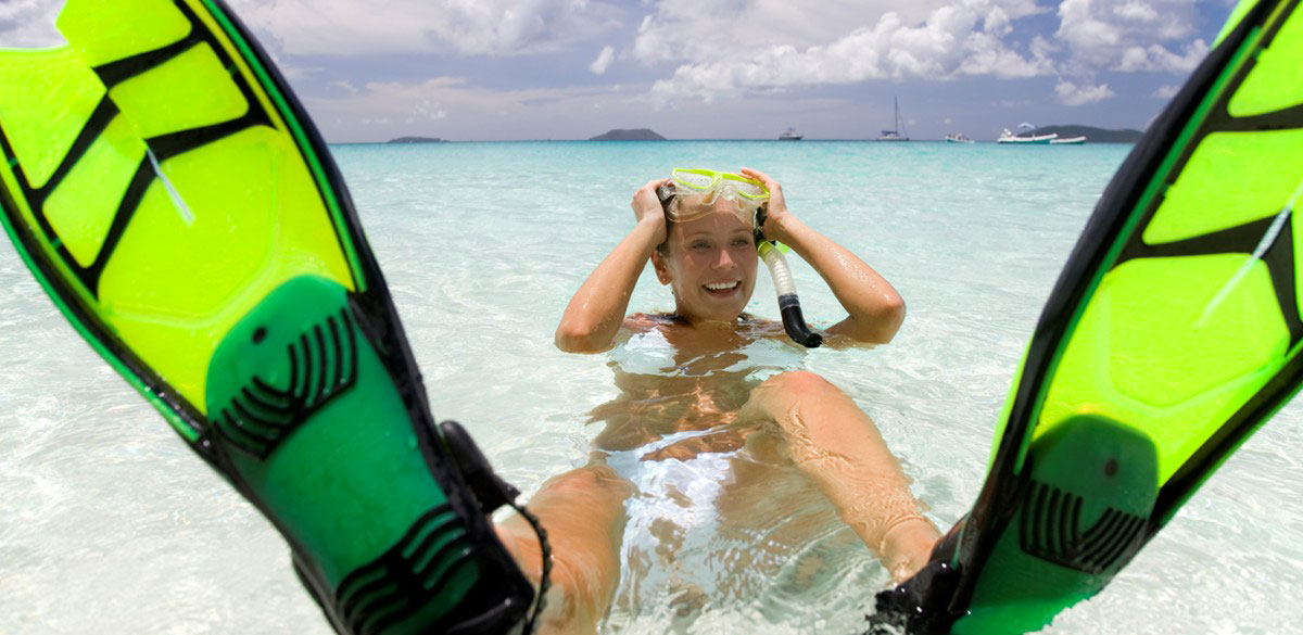 A snorkeller resting on white sand in a crystal clear sea, flippers above the water in the foreground