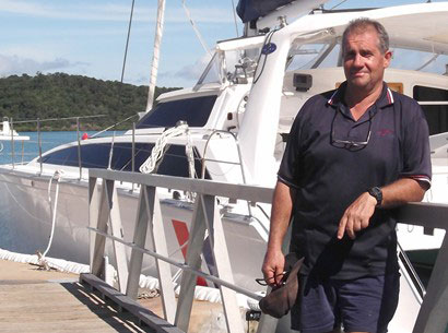 Head mechanic Steve Miller beside a Whitsunday Rent A Yacht sailing catamaran