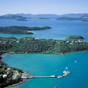 Aerial view of Shute Harbour and surrounding coast with the Whitsunday Rent A Yacht base and jetty in the foreground