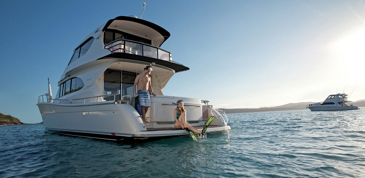 A man and woman prepare to go snorkelling from the back of motor cruiser in the Whitsundays