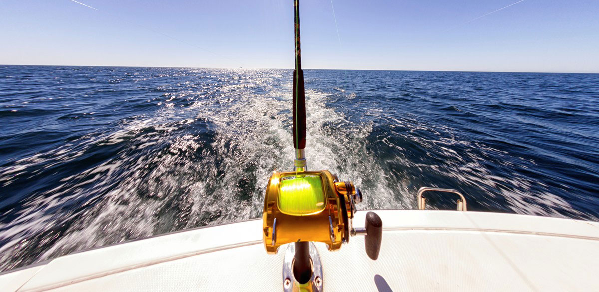 A fishing rod on the back of a Whitsunday Rent A Yacht charter boat with open water and clear horizon beyond