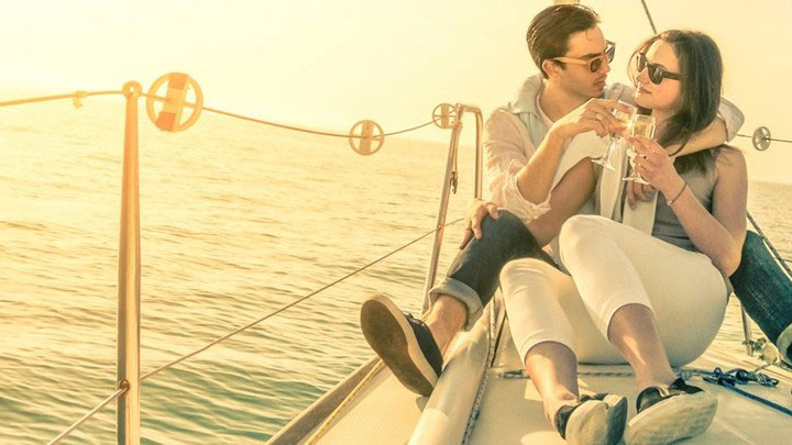 A couple drinking champagne at the prow of a Whitsunday Rent A Yacht charter yacht, bathed in yellow sunlight
