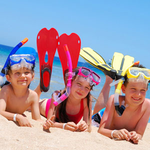 Three children lying on Chalkies Beach in snorkels, masks and flippers