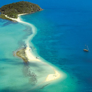 Aerial view of Langford Island in the Whitsundays with yacht offshore
