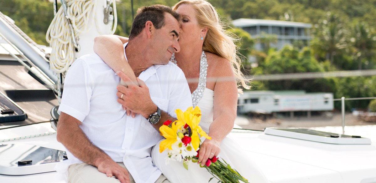 A bride and groom embrace on the deck of a Whitsunday Rent a Yacht sailing catamaran
