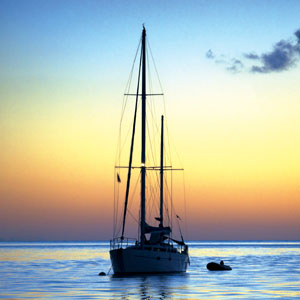Silhouette of moored yacht and dinghy at sunset